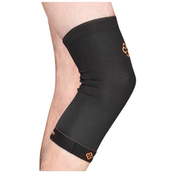 A close up on a black compression knee sleeve being on the right leg of someone standing in front of a white background