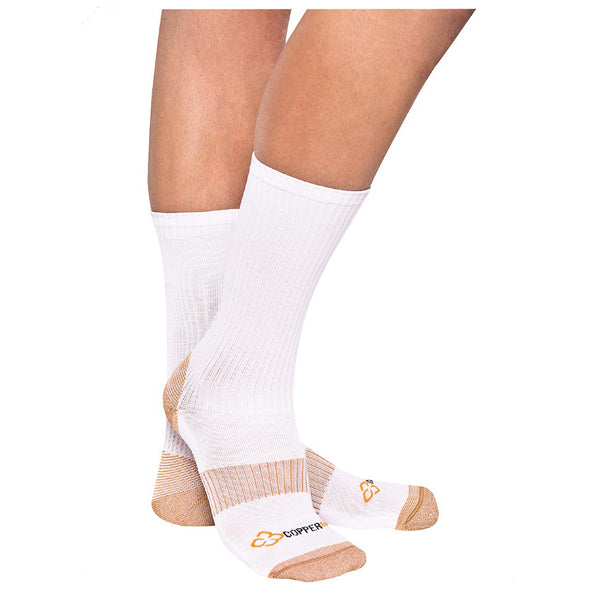 A pair of legs from the knee down wearing copper compression calf high socks in front of a white background