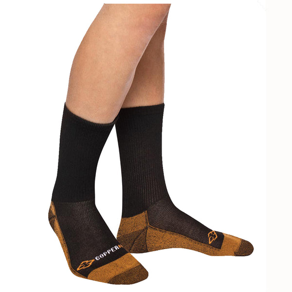Thick black and copper compression socks on a person's feet standing in front of a white background