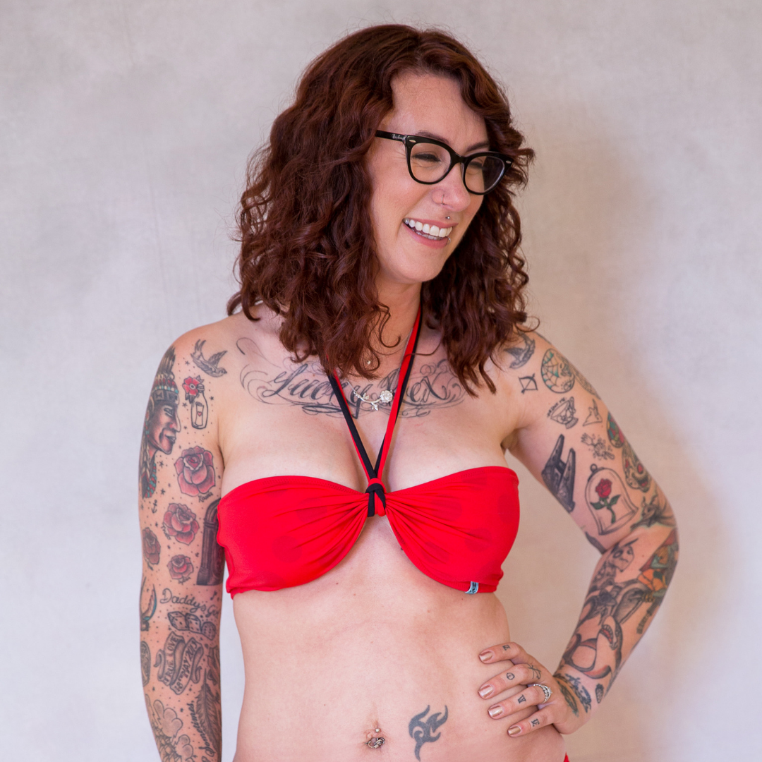 A lady with curly bronze coloured hair, glasses and tattoes on her arms, chest and hands is smiling as she stands with her hand on her hip in Mermaid In England's Bermuda Betty red bandeau bikini. There are red and black ties that go around her neck to provide support but also to change the look when wearing the bikini. The red bikni reveals black polka pattern when it gets wet. We call it colour change swimwear. It's the magic of each design at Mermaid in England. Ethically handmade in Great Britain.