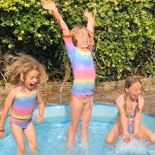 Three girls are jumping and splashing up and down in a passling pool and having a great time. They are all wearing magic colour change swimwear as it changes to a rainbow colour in the water.