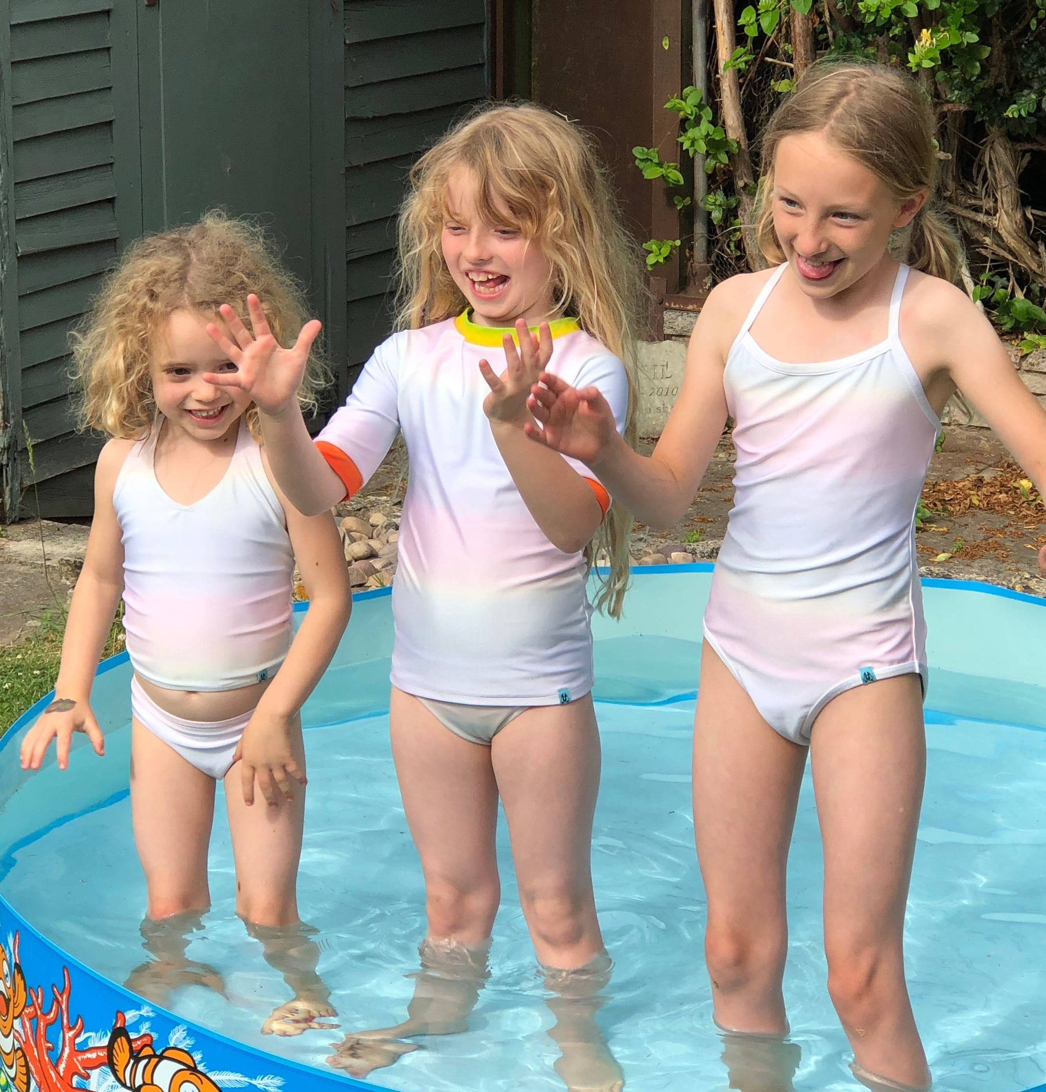 Three girls in a paddling pool are all wearing different kinds of swimming costumes. One girl is wearing a tankini and brief set, one girls in wearing a rash vest and brief set and one girl is wearing a one piece swimming costume. All the wimwear is part of Mermaid In England's children's collection. Their swimwear changes colour in water and the Inner Glow transform from white to rainbow in water. All ethically handsewn in Britain.