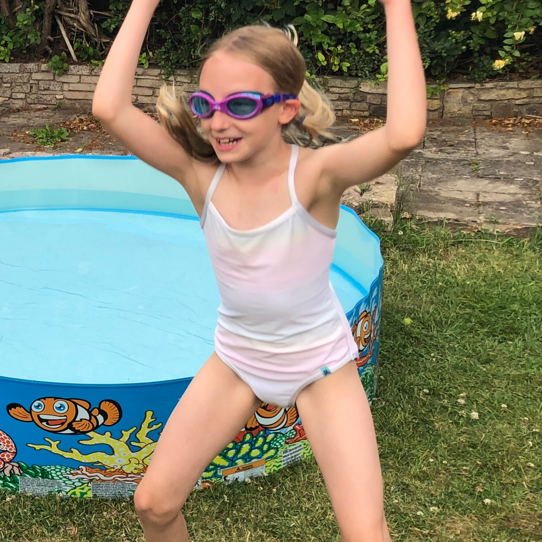 Girl playing around in the garden wearing goggles and a white swimming costume from Mermaid In England's Inner Glow collection. The swimsuit changes colour in water to a magical rainbow. Ethically handmade in Britain.