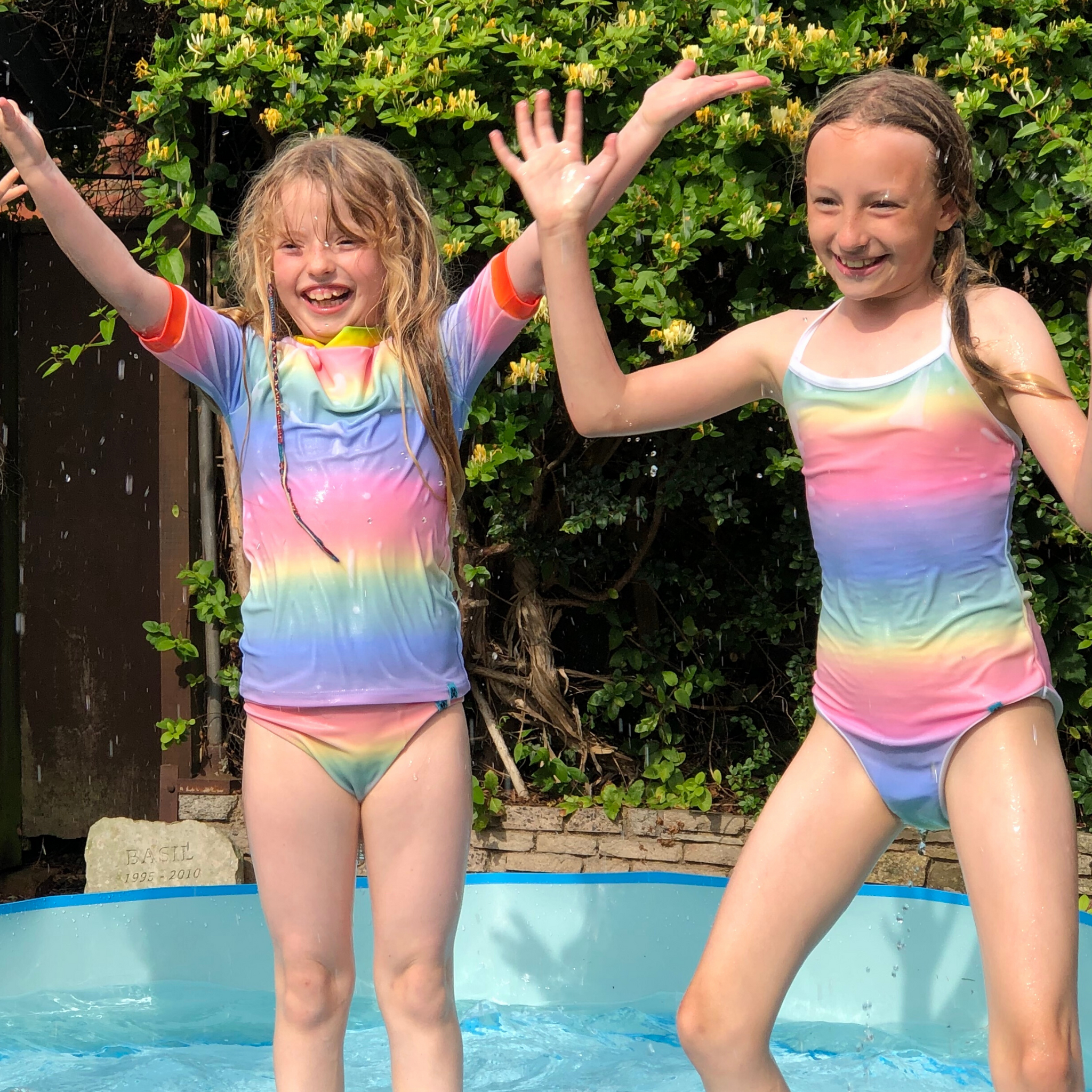 Two girls are smiling and having fun in their rainbow colour change swimming costumes, splashing in the paddling pool. One is wearing a rash vest and plain brief set and the other is wearing a one piece swimming costume. The swimwear is all from Mermaid In England Colour Change Swimwear Inner Glow collection. Transforming colour from white to rainbow in water.