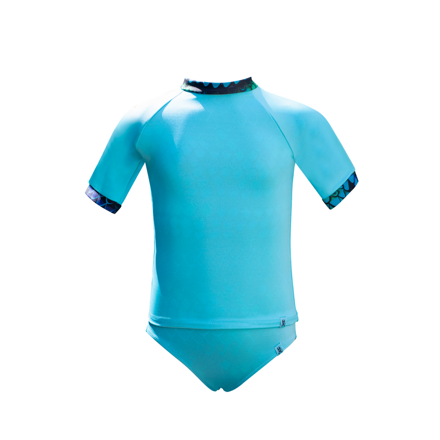 This Mermaid In England children's rash vest is a necessity in the sun. Providing excellent sun protection the swim top is an aqua blue, short sleeved but longer in the body to ensure coverage. Ethically made in Great Britain, the rash vest reveals a mermaid scale design when in water. We call this magic colour change swimwear.