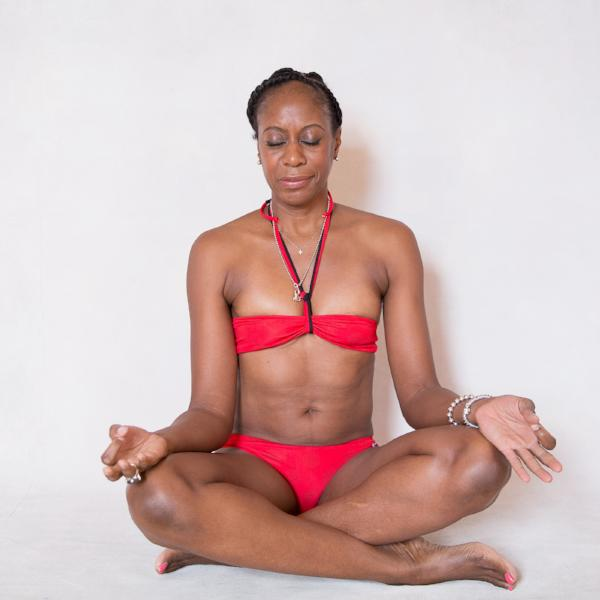 Donna Noble, a yoga instructor from London, is sitting in a cross legged position the her eyes closed and her palms facing up on her knees. She is wearing Mermaid In England's Bermuda Betty red bandeau colour change bikini. She looks very peaceful and content.