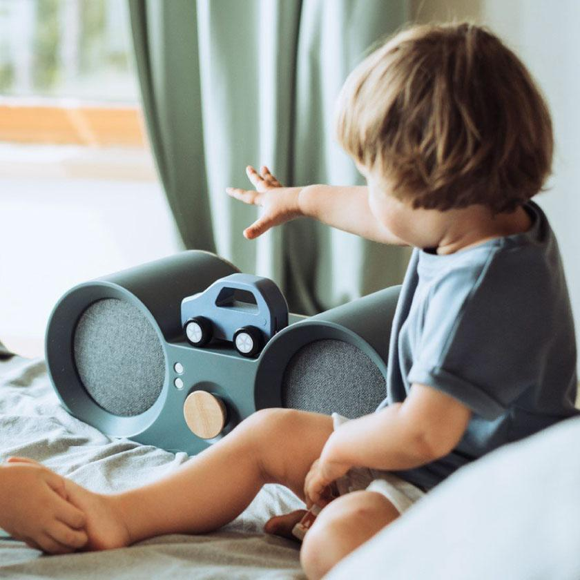 Babbit premium kids speaker. A boy plays music by placing a toy car on the speaker.