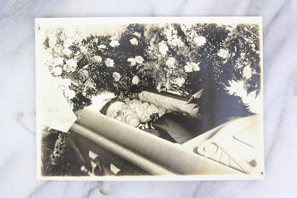 Postmortem Photograph of a Man in His Coffin Surrounded by Flowers