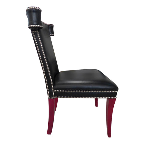 Black leather chair with silver studded detail and red legs