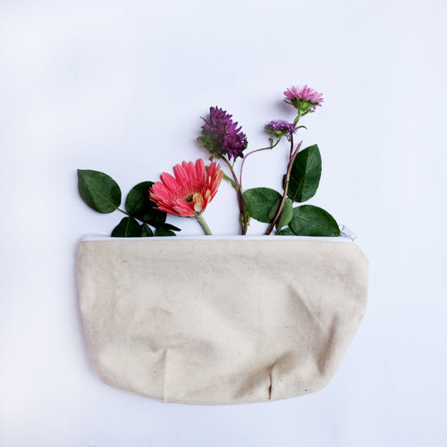 Canvas cosmetic bag with flowers and leaves stocking out of it.