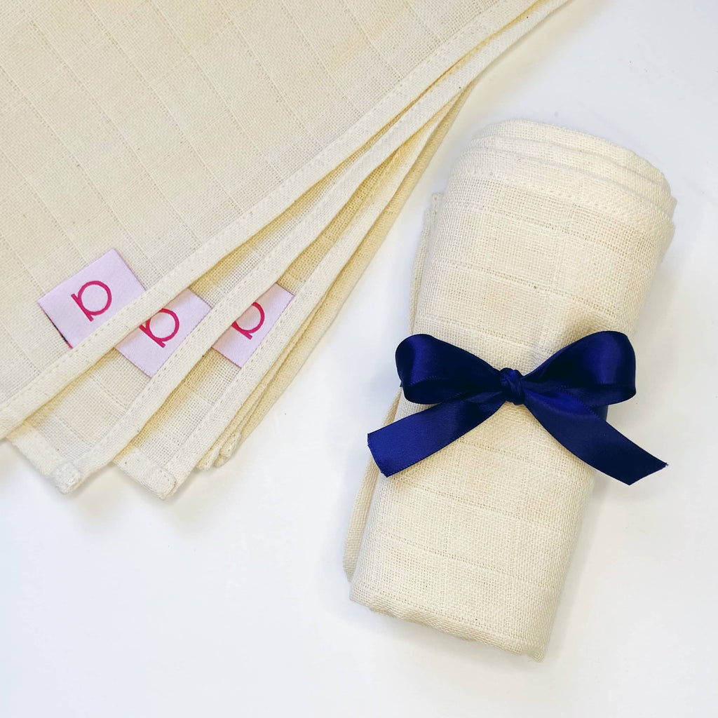 Bundle of Amaranthine muslin cloths, tied with a navy ribbon. Also showing single cloths with Amaranthine branding.
