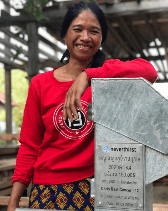 woman smiling and leaning on clean-water well