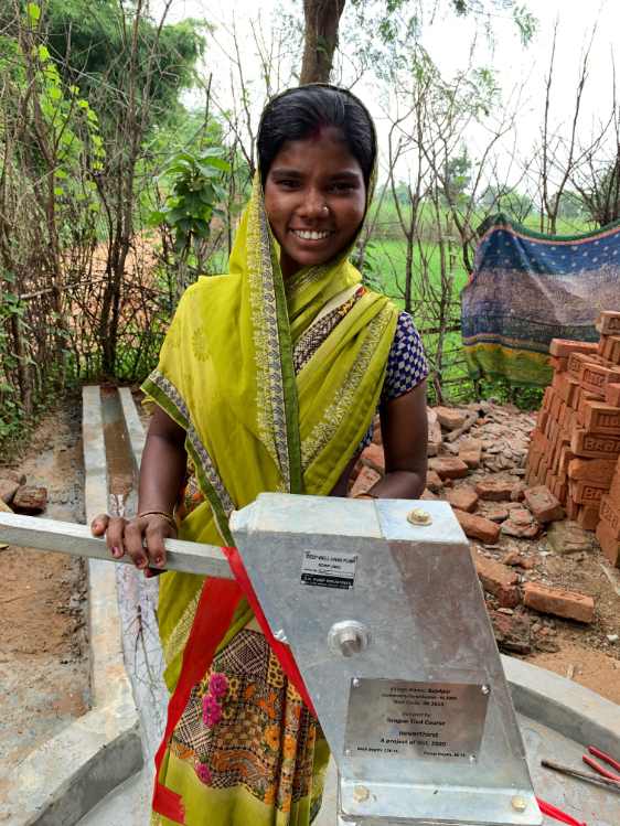 woman smiling and leaning on neverthirst clean-water well