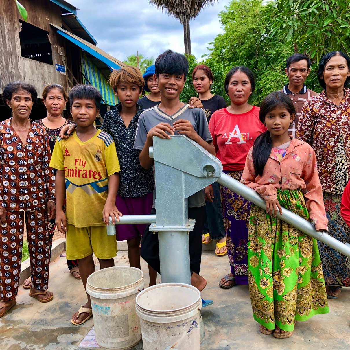 neverthirst group in front of a handpump