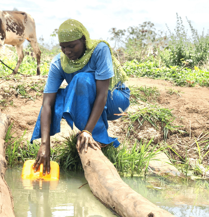 woman collecting water by stream in neverthirst jerry can