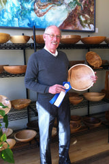 PHOTO: Jan Close, with his award-winning Tiger Maple Salad Bowl and Blue Ribbon from the Northeastern Woodworkers Association Showcase, standing in front of his collection of woodturnings at Maple Run Emporium.