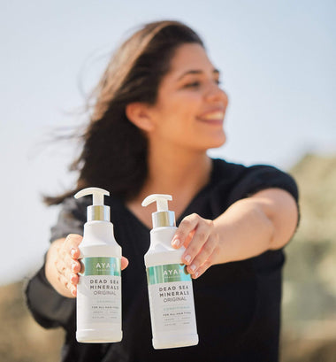 Woman Holding 2 Bottles of Dead Sea Minerals Conditioner