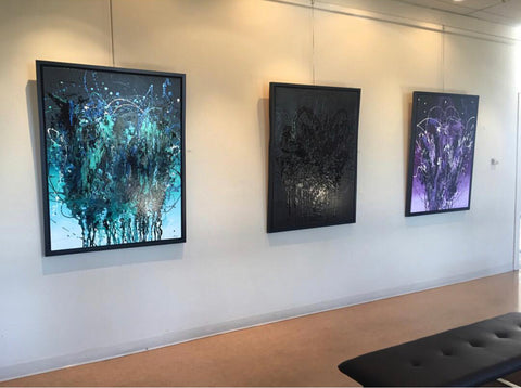 Three large abstract paintings in an art gallery