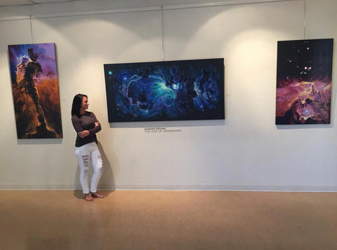 Artist Sarazen Brooks with her paintings at an art show