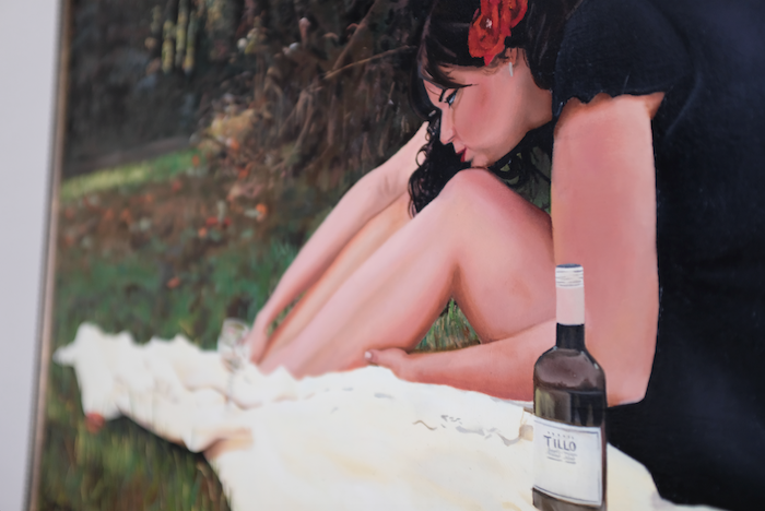 Portrait of a woman sitting in a field drinking wine