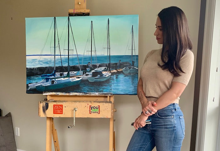 Artist Sarazen Brooks with a painting of sailboats