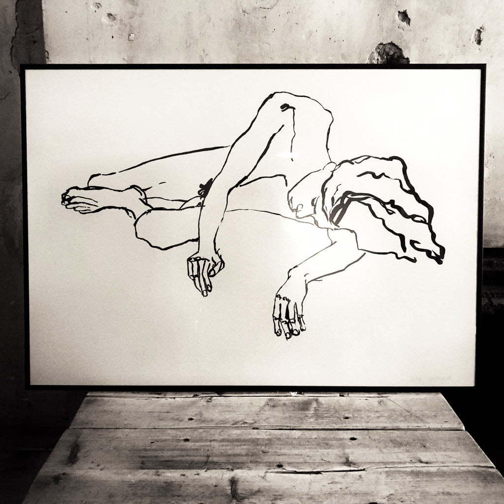 A framed drawing propped up on a table, of a man sleeping, but artist Kris Lamorena.