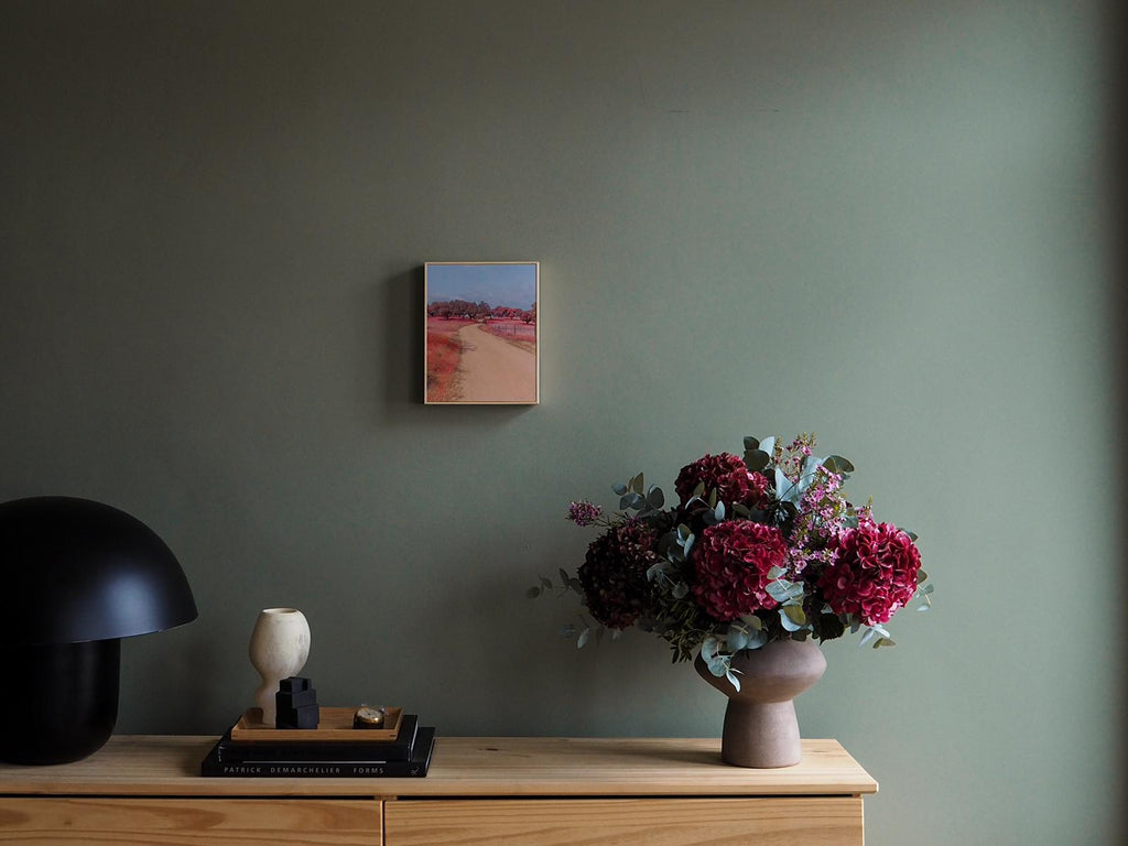 An image by Teresa Freitas, hanging next to a vase of flowers.