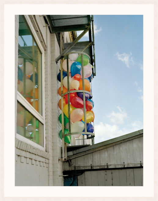 A colourful image of balloons alongside a building, by Polish artist Oliver Schwarzwald. The image is presented in a white wooden frame.