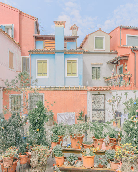 An image of a small garden and some houses, in bright and optimistic hues, by emerging Portuguese artist Teresa Freitas.