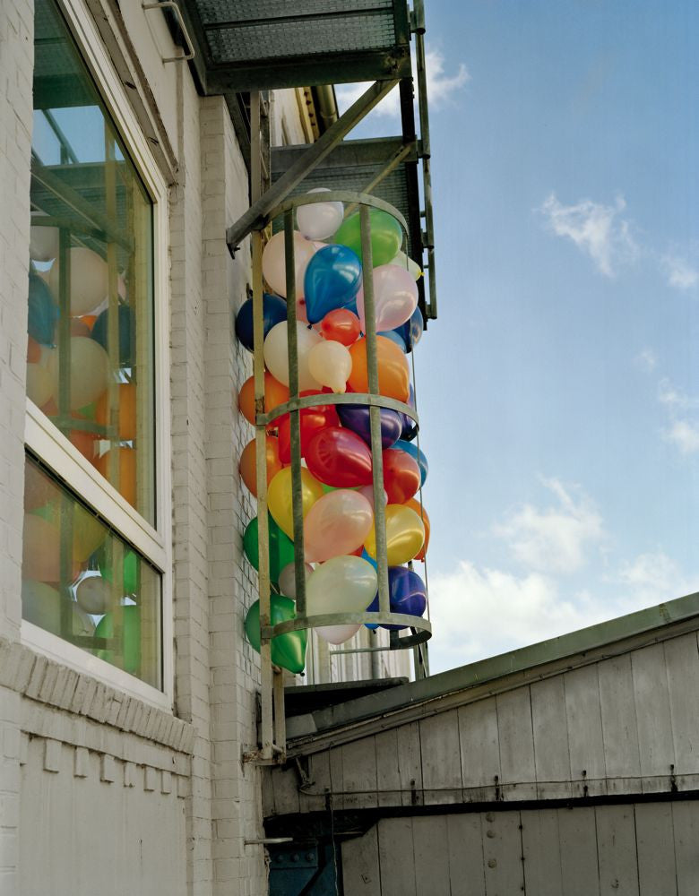 A colourful image of balloons alongside a building, by Polish artist Oliver Schwarzwald.