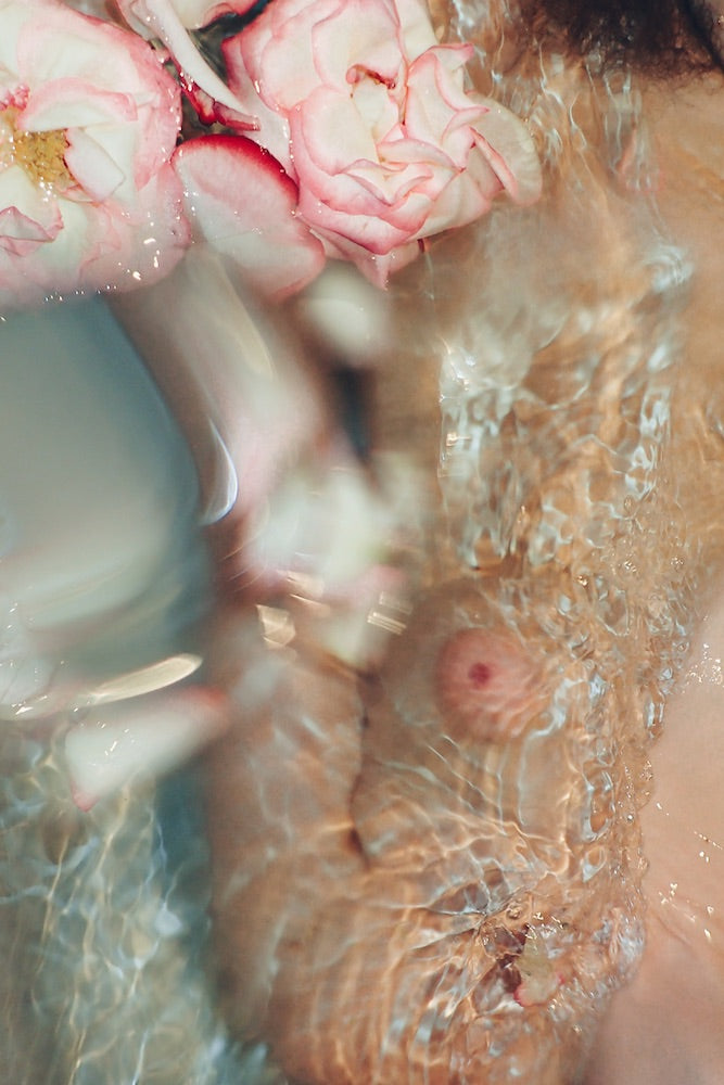 An image of a woman's naked torso in the bath, with pink flowers, taken by emerging Dutch artist Lana Prins.
