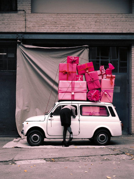 A image of a Mini car with pink presents piled on top and a woman leaning inside, by Polish artist Oliver Schwarzwald.