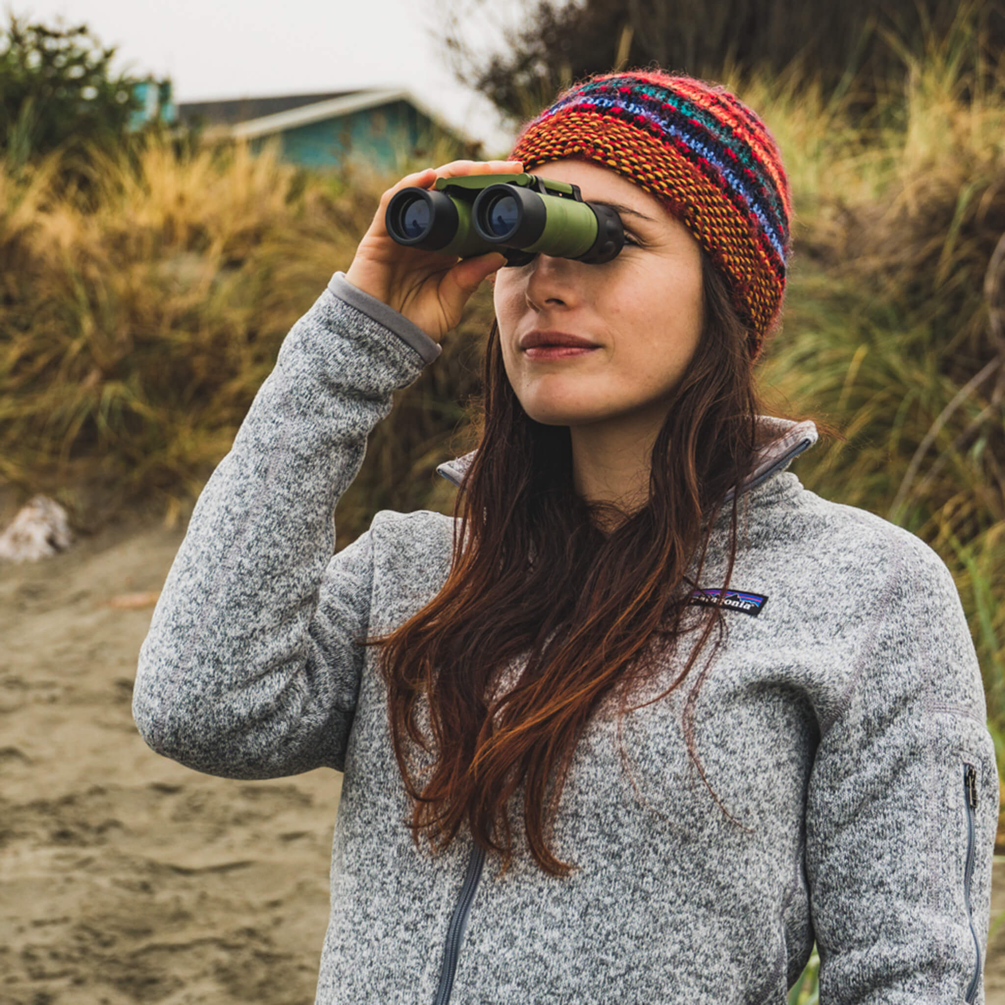 Woman looking out from beach with binoculars