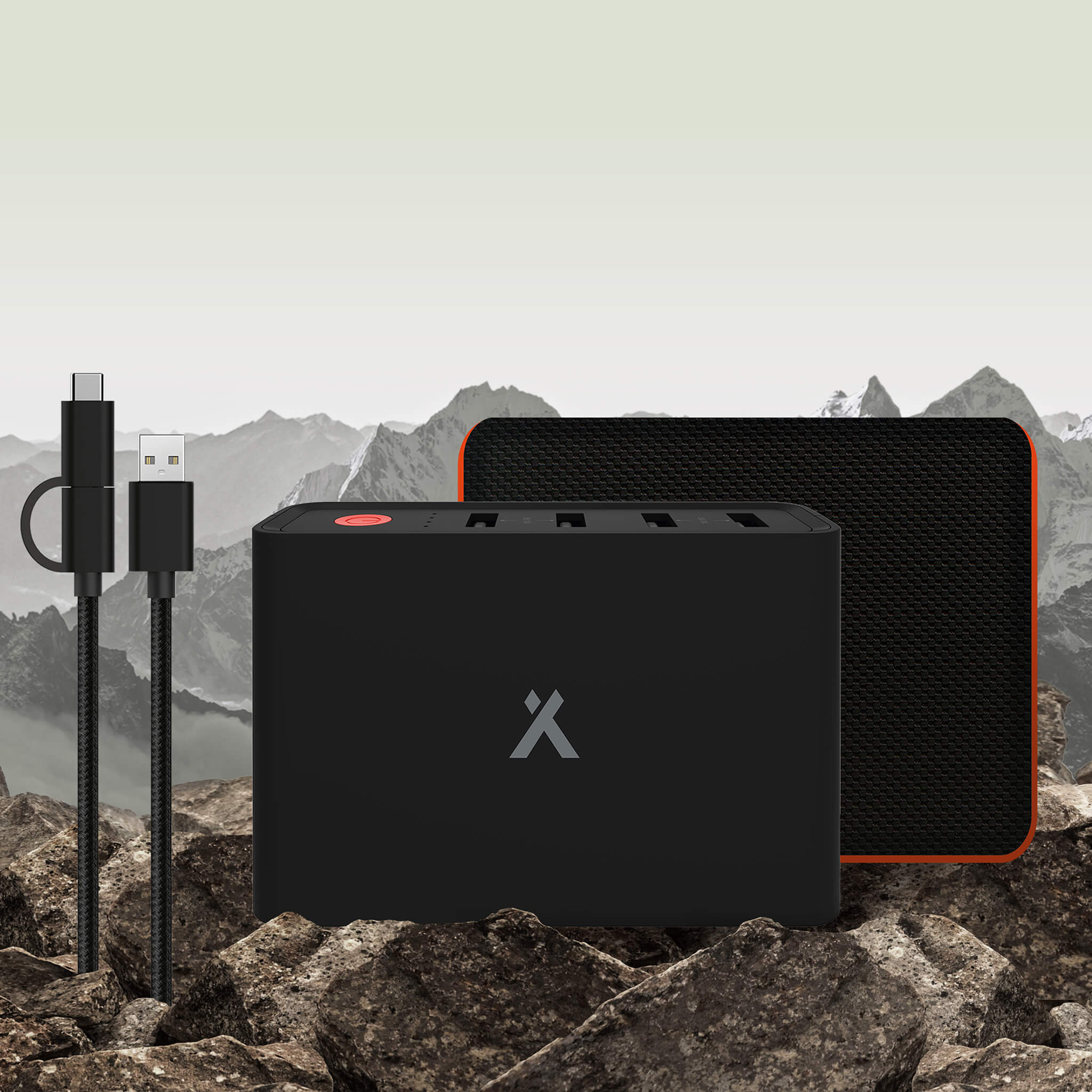 The Bear Grylls Power bank on rocks in mountain range