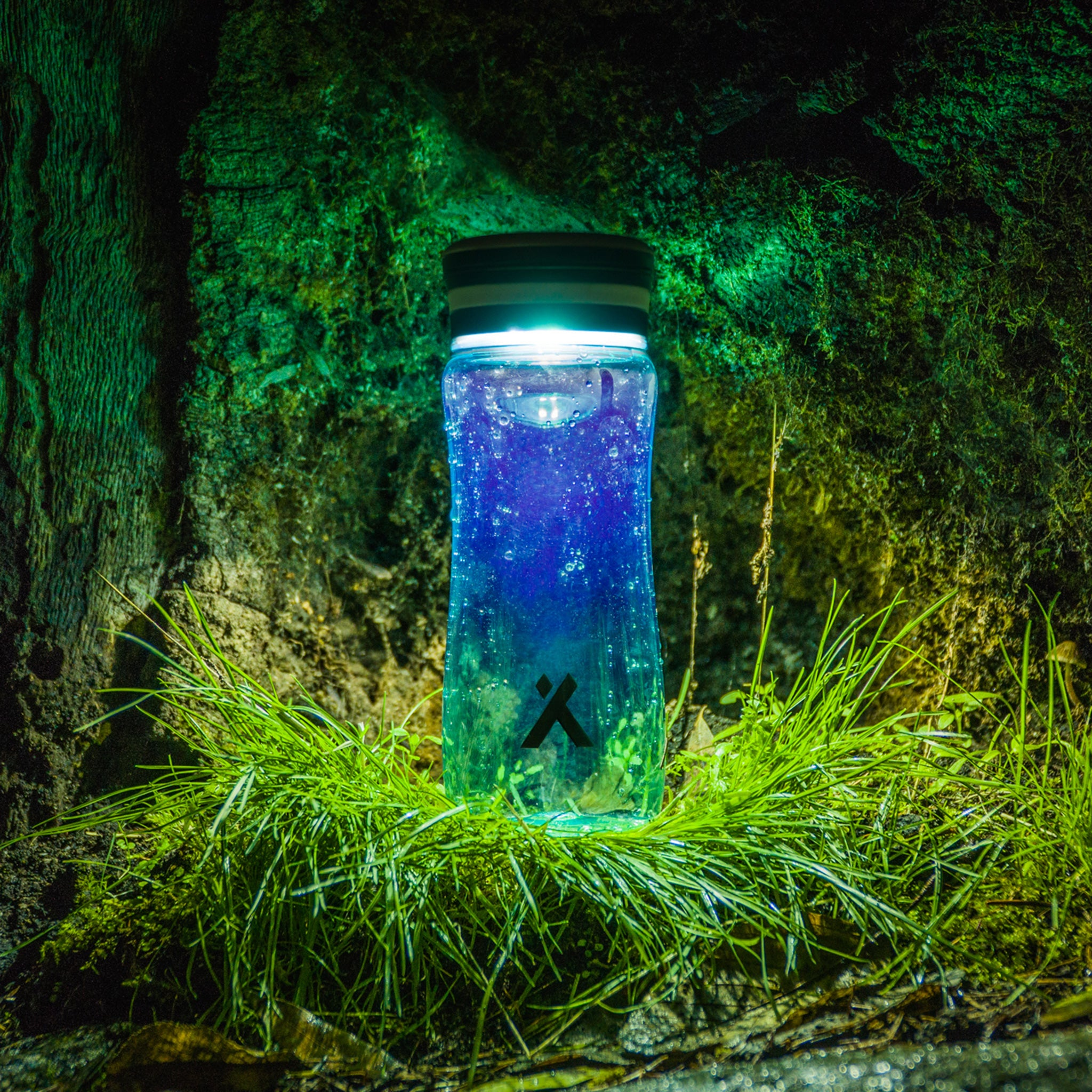 Bear Grylls Solar Bottle lighting up a dark forest