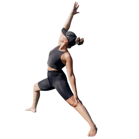 Women in triangle yoga pose, wearing a womens black Ponyback ponytail hat with her hair in a bun