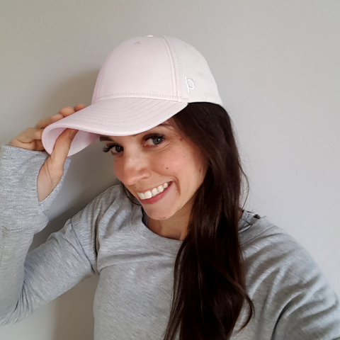 Women wearing a pink Ponyback ponytail hat with a white embroidered logo