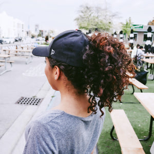 Women with black curly hair is wearing a black ponyback ponytail hat with her hair pulled into a pony tail. The magnetic back opening of this women's hat is in open position allowing the wearer to pull her hair through.
