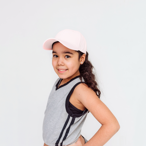 Girl wearing a pink Ponyback ponytail hat, she has a low ponytail and is wearing a pink shirt, there is a white P logo for Ponyback on the left side of the hat
