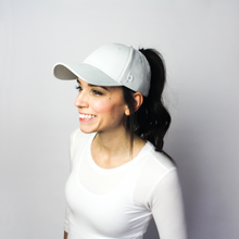 Load image into Gallery viewer, Woman wearing the Ponyback grey pink ponytail hat, this is the front view of the woman, her hair is up and her ponytail pulled through the back opening.
