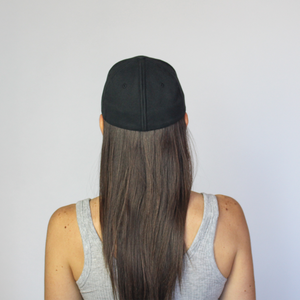 Back view of women wearing Ponyback ponytail hat in black in closed position with hair down