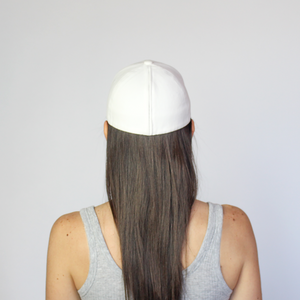 Back view of a women wearing a white Ponyback ponytail hat with hair in a down position.