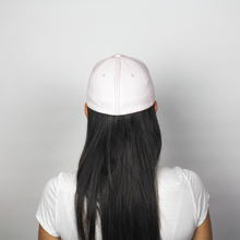 Load image into Gallery viewer, Woman wearing the Ponyback primrose pink ponytail hat, this is the back view of the woman, her hair is down and not using the opening. The magnetic back closure is closed showing that this hat looks like a normal baseball hat.
