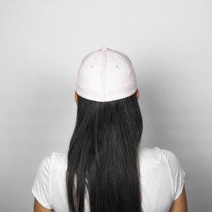 Woman wearing the Ponyback primrose pink ponytail hat, this is the back view of the woman, her hair is down and not using the opening. The magnetic back closure is closed showing that this hat looks like a normal baseball hat.