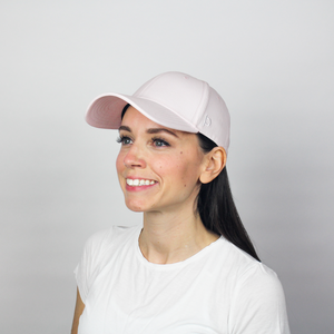 Woman wearing the Ponyback primrose pink ponytail hat, this woman has her hair down not using the closeable opening in the back.