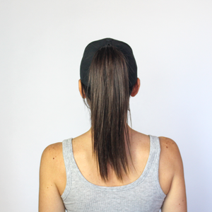 Back view of women wearing the black Ponyback ponytail hat, with back opening in open position and ponytail pulled through.
