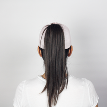 Load image into Gallery viewer, Woman wearing the Ponyback primrose pink ponytail hat, this woman's pony is up high and being pulled through the back opening.