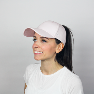 Woman wearing the Ponyback primrose pink ponytail hat, this women's ponytail is up high and pulled through the back opening.
