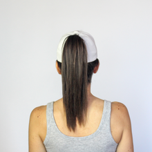 Load image into Gallery viewer, Back view of a women wearing a white Ponyback ponytail hat with hair in a high ponytail pulled through the back opening of the hat.
