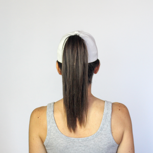 Back view of a women wearing a white Ponyback ponytail hat with hair in a high ponytail pulled through the back opening of the hat.